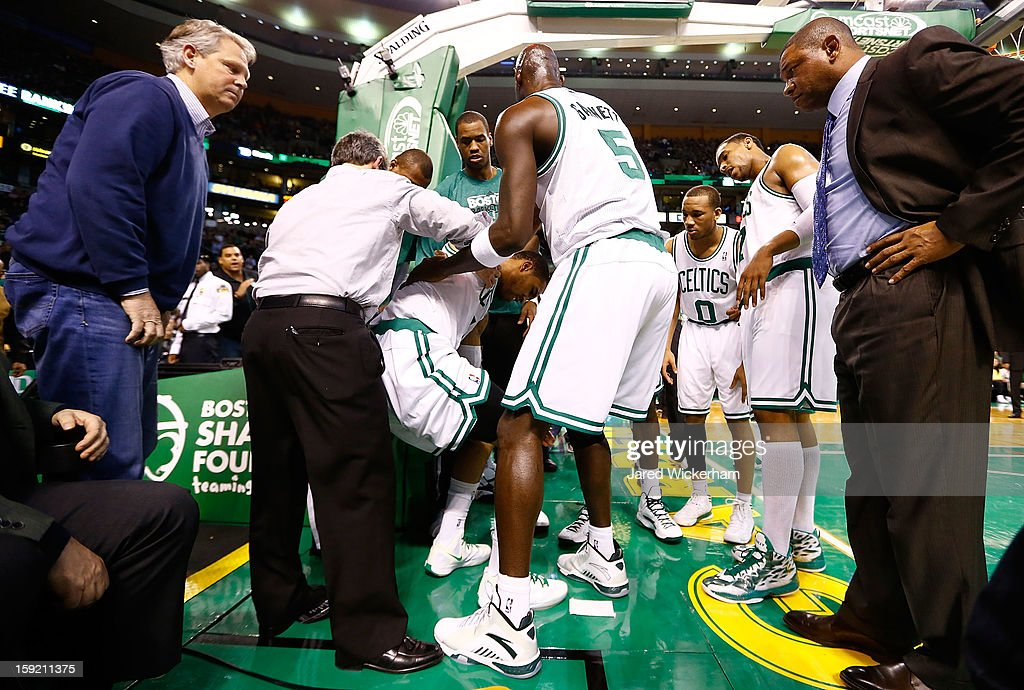 Head coach Doc Rivers looks on as Courtney Lee #11 of the Boston Celtics is helped up by teammate Kevin Garnett #5 after injuring himself on a court side seat after going up for a shot against the Phoenix Suns during the game on January 9, 2013 at TD Garden in Boston, Massachusetts.