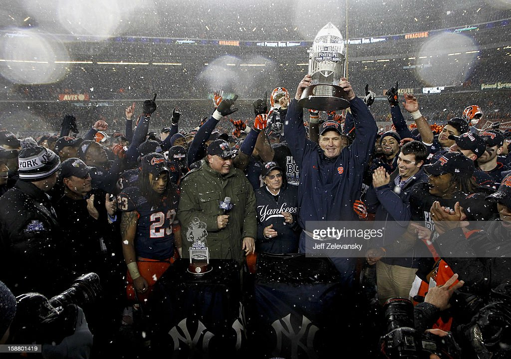 Head coach Doug Marrone of the Syracuse Orange hoists the trophy after victory over the West Virginia Mountaineers in the New Era Pinstripe Bowl at Yankee Stadium on December 29, 2012 in the Bronx borough of New York City.
