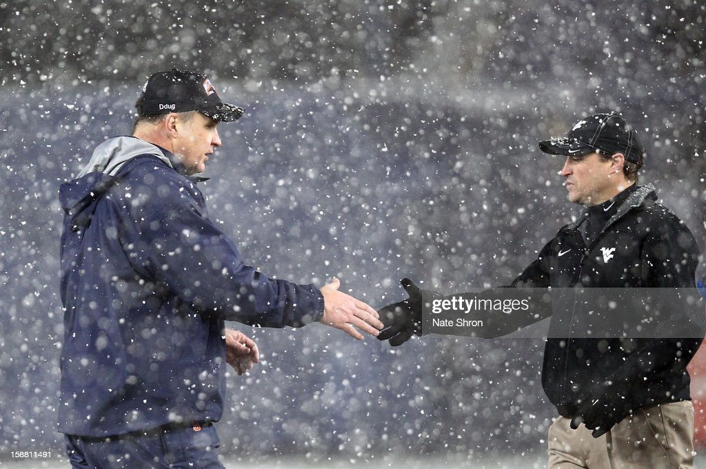Head coach Doug Marrone (L) of the Syracuse Orange shakes hands with head coach Dana Holgorsen (R) of the West Virginia Mountaineers after the New Era Pinstripe Bowl at Yankee Stadium on December 29, 2012 in the Bronx borough of New York City.