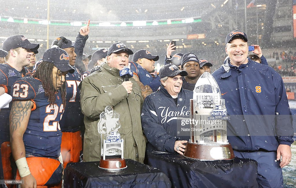 Head coach Doug Marrone (R) of the Syracuse Orange stands with teamates as they receive the trophy after their win over the West Virginia Mountaineers during the New Era Pinstripe Bowl at Yankee Stadium on December 29, 2012 in the Bronx borough of New York City.