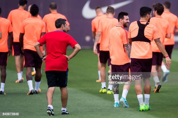 Head coach Ernesto Valverde Lionel Messi and Luis Suarez of FC Barcelona walk during a training session ahead of the UEFA Champions League Group D...