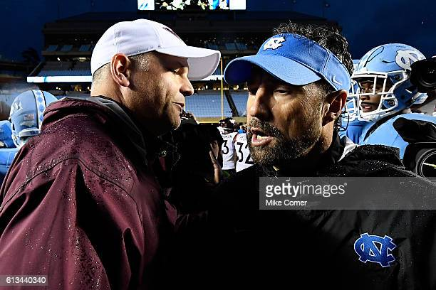 Head coach football Larry Fedora of the UNC Tar Heels shakes hands with head coach Justin Fuente of the Virginia Tech Hokies following their game at...