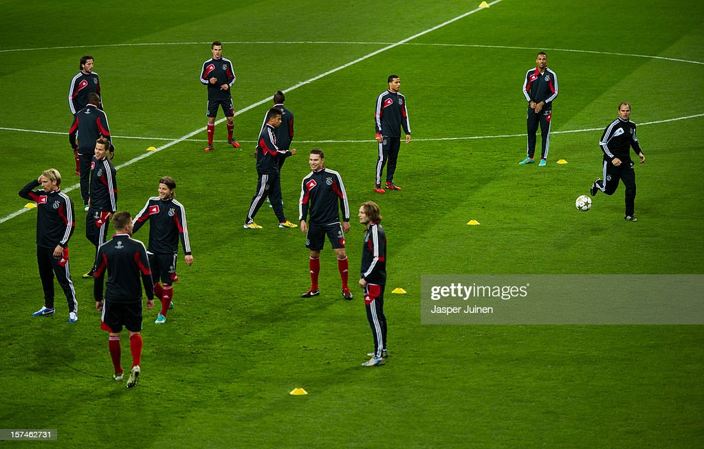 Head coach <a gi-track='captionPersonalityLinkClicked' href=/galleries/search?phrase=Frank+De+Boer&family=editorial&specificpeople=1006742 ng-click='$event.stopPropagation()'>Frank De Boer</a> (R) of Ajax runs for the ball besides his players during a training session ahead of the UEFA Champions League match between AFC Ajax and Real Madrid CF at the Estadio Santiago Bernabeu on December 3, 2012 in Madrid, Spain.