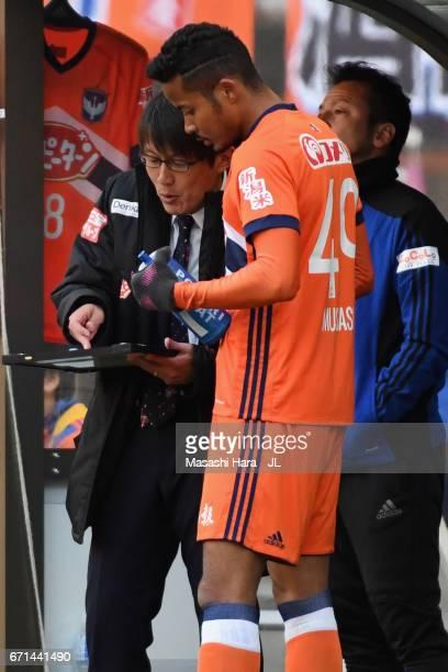 Head coach Fumitake Miura of Albirex Niigata speaks to substitute Musashi Suzuki during the JLeague J1 match between Albirex Niigata and FC Tokyo at...