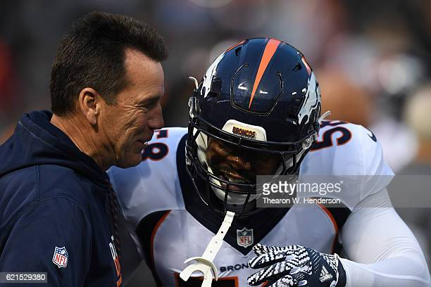 Head coach Gary Kubiak and Von Miller of the Denver Broncos talk on the field prior to the game against Oakland Raiders at OaklandAlameda County...