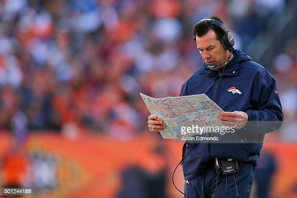 Head coach Gary Kubiak of the Denver Broncos looks over a play chart on the sideline during game against the Oakland Raiders at Sports Authority...