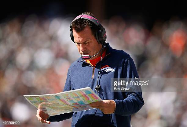 head coach Gary Kubiak of the Denver Broncos references his play card in the second quarter against the Oakland Raiders at Oco Coliseum on October 11...