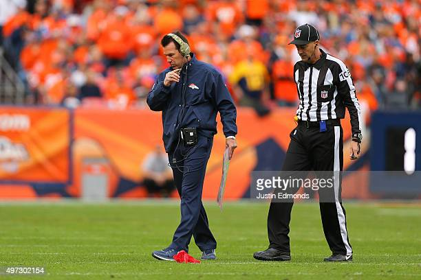 Head coach Gary Kubiak of the Denver Broncos walks on the field after throwing a challenge flag near line judge Gary Arthur during the second quarter...