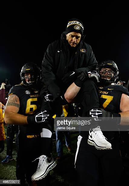 Head coach Gary Pinkel of the Missouri Tigers is carried off the field by offensive lineman Brad McNulty and offensive lineman Evan Boehm after the...
