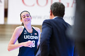 head coach Geno Auriemma high fives Breanna Stewart of the Connecticut Huskies as she leaves the game against the Colgate Raiders during the second...