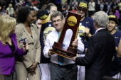 Head coach Geno Auriemma of the Connecticut Huskies holds the trophy after defeating the Notre Dame Fighting Irish 79 to 58 in the NCAA Women's Final...