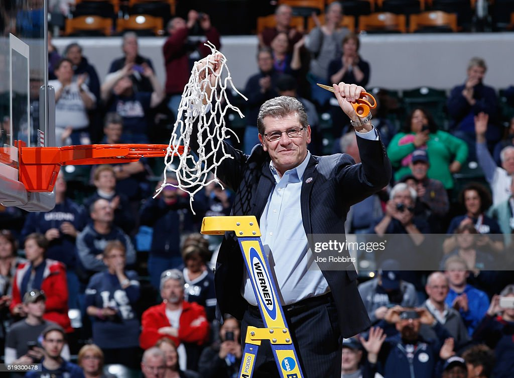 Head coach Geno Auriemma of the Connecticut Huskies holds up the net after cutting it down following their 8251 victory over the Syracuse Orange to...
