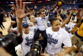 Head coach Geno Auriemma of the Connecticut Huskies is carried off the court by his players after defeating the Louisville Cardinals winning his...