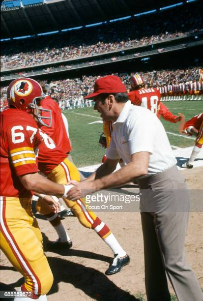 Head coach George Allen of the Washington Redskins shakes hands with Rusty Tillman during player introduction prior to the start of an NFL football...