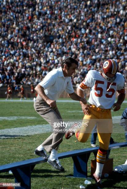 Head coach George Allen of the Washington Redskins steps over the bench with linebacker Chris Hanburger during an NFL football game circa 1972 Allen...