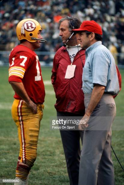Head coach George Allen of the Washington Redskins talks with quarterback Billy Kilmer on the sidelines during an NFL football game circa 1971 at RFK...