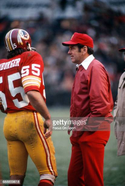 Head coach George Allen of the Washington Redskins talks with linebacker Chris Hanburger on the sidelines during an NFL football game circa 1972 at...