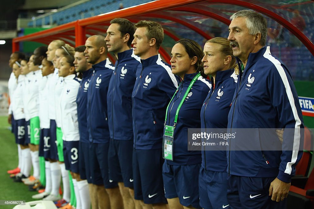 Head coach Gilles Eyquem of France and team members sing the national anthem prior to the FIFA U-20 Women's World Cup Canada 2014 3rd place match between Korea DPR and France at Olympic Stadium on August 24, 2014 in Montreal, Canada.