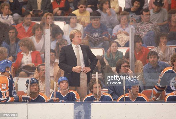 Head coach Glen Sather of the Edmonton Oilers watches from the bench with seated players including Wayne Gretzky during an away game against the New...