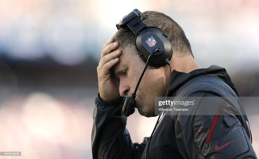 Head coach Greg Schiano holds his head during the fourth quarter of their 233 loss to the New England Patriots at Gillette Stadium on September 22...