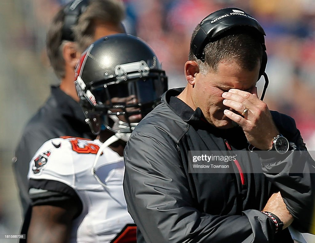 Head coach Greg Schiano of the Tampa Bay Buccaneers hangs his head during the first half against the New England Patriots at Gillette Stadium on...