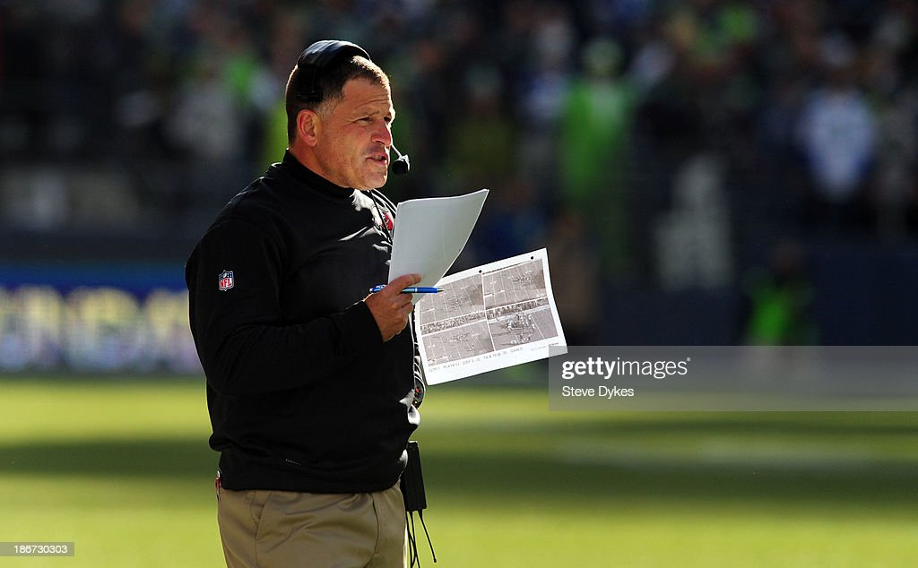 Head coach Greg Schiano of the Tampa Bay Buccaneers looks over his play sheets during the first quarter of the game against the Seattle Seahawks at...