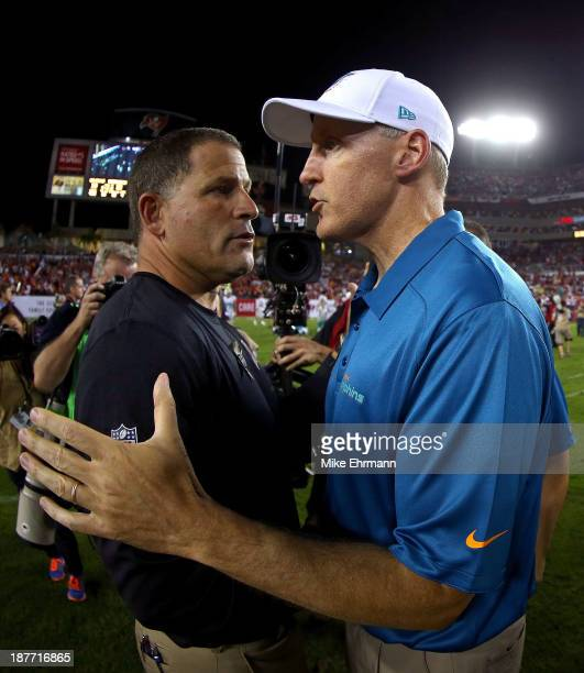 Head coach Greg Schiano of the Tampa Bay Buccaneers shakes hands with head coach Joe Philbin of the Miami Dolphins during a game at Raymond James...