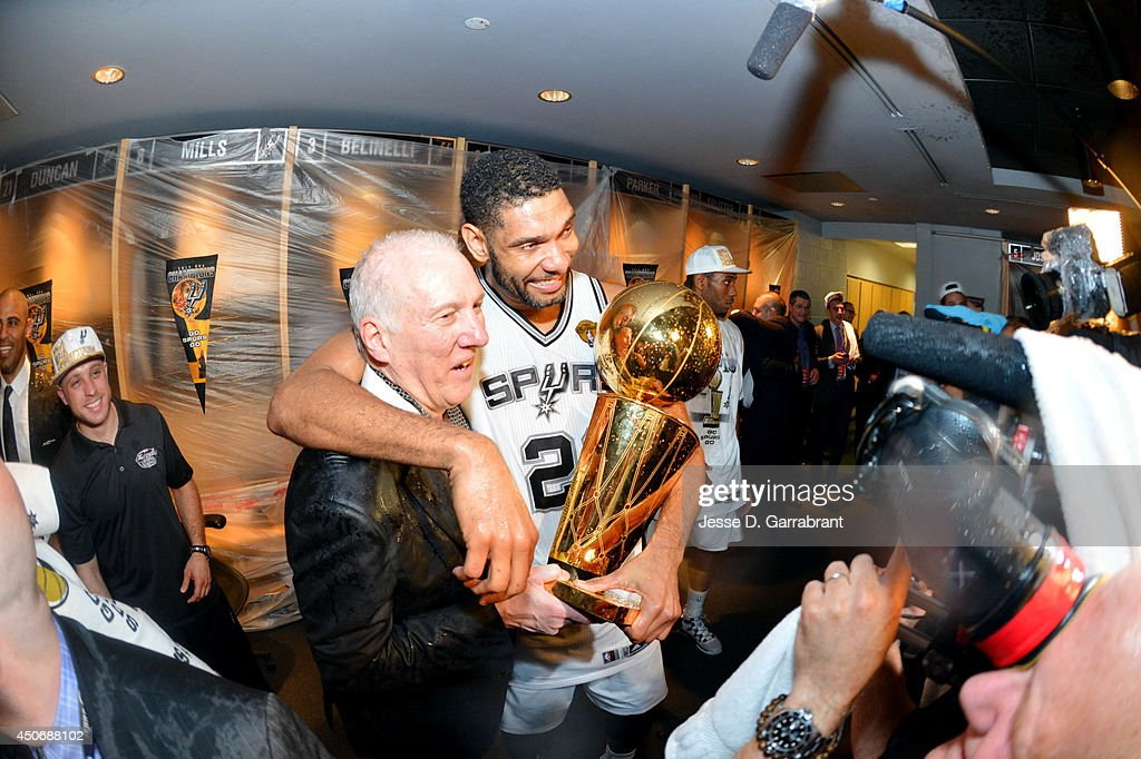 Head Coach <a gi-track='captionPersonalityLinkClicked' href=/galleries/search?phrase=Gregg+Popovich&family=editorial&specificpeople=202904 ng-click='$event.stopPropagation()'>Gregg Popovich</a> and <a gi-track='captionPersonalityLinkClicked' href=/galleries/search?phrase=Tim+Duncan&family=editorial&specificpeople=201467 ng-click='$event.stopPropagation()'>Tim Duncan</a> #21 of the San Antonio Spurs celebrate in the locker room with the Larry O'Brien trophy after defeating the Miami Heat to win the 2014 NBA Finals in Game Five of the 2014 NBA Finals on June 15, 2014 at AT&T Center in San Antonio, Texas.