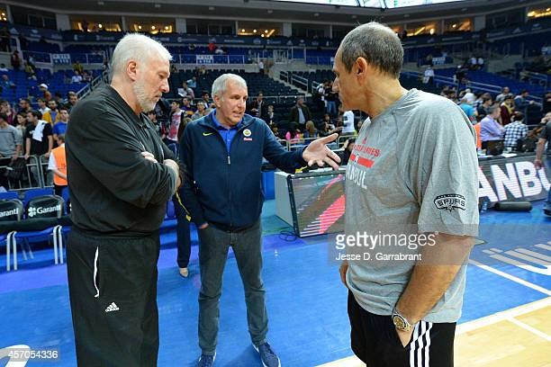 Head Coach Gregg Popovich Assistant Coach Ettore Messina of the San Antonio Spurs and Zeljko Obradovic of Fenerbahce Ulker talk prior to a game as...