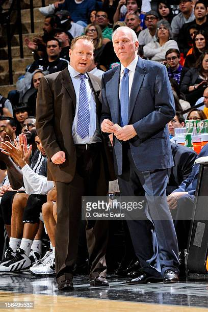 Head Coach Gregg Popovich of the San Antonio Spurs right speaks with assistant coach Mike Budenholzer during a game against the New York Knicks on...