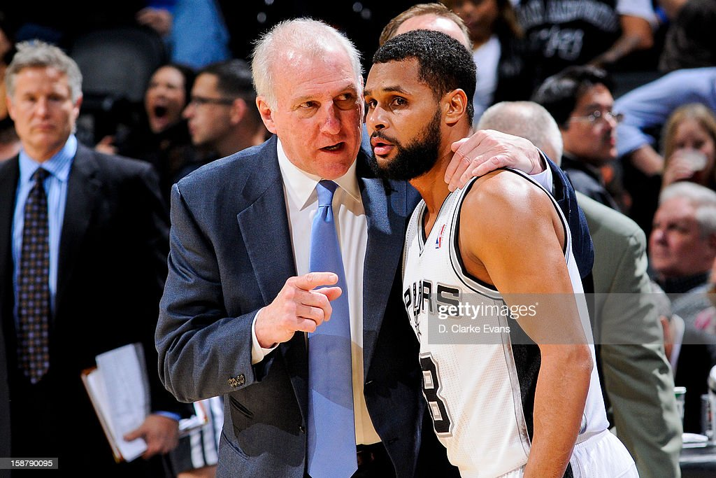 Head Coach Gregg Popovich of the San Antonio Spurs speaks to Patty Mills #8 during a game against the Houston Rockets on December 28, 2012 at the AT&T Center in San Antonio, Texas.