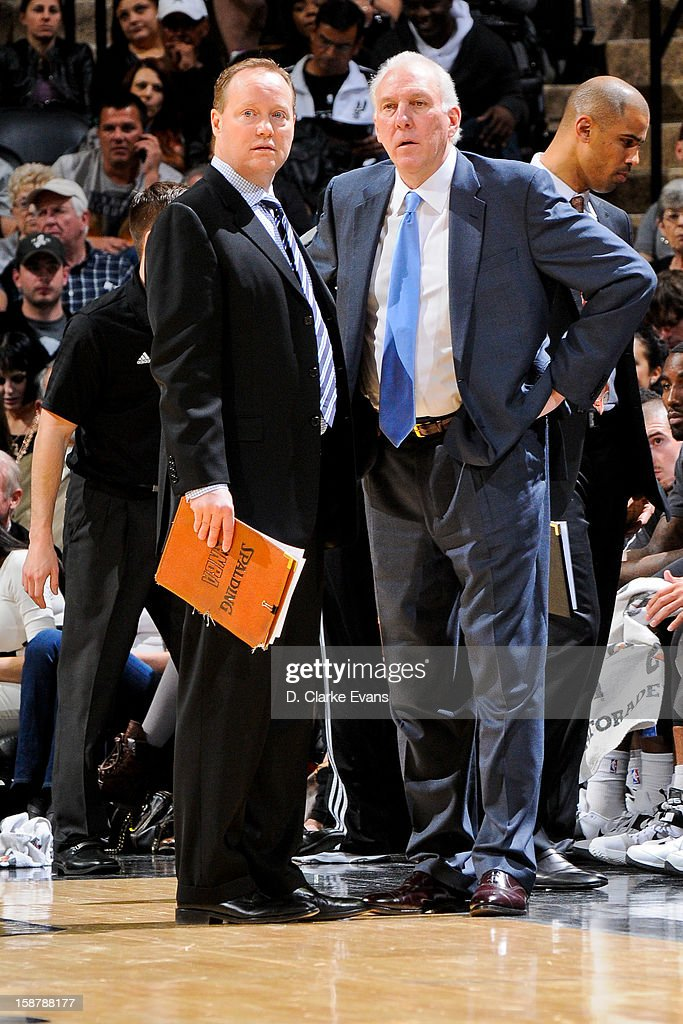 Head Coach Gregg Popovich of the San Antonio Spurs speaks with assistant coach Mike Budenholzer during a game against the Houston Rockets on December 28, 2012 at the AT&T Center in San Antonio, Texas.