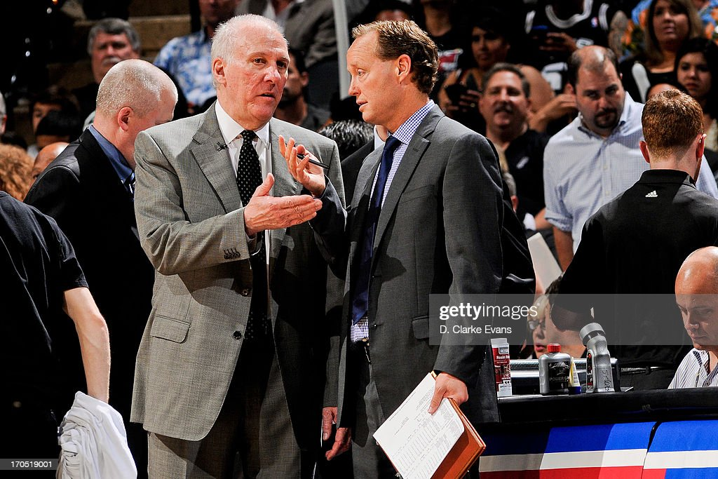 Head Coach Gregg Popovich of the San Antonio Spurs speaks with assistant coach Mike Budenholzer as the team plays the Miami Heat during Game Four of...