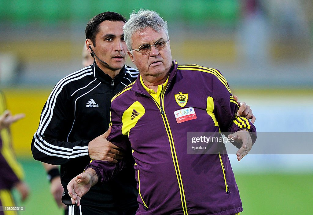 Head coach Guus Hiddink of FC Anzhi Makhachkala is held by an official during the Russian Premier League match between FC Anzhi Makhachkala and FC...