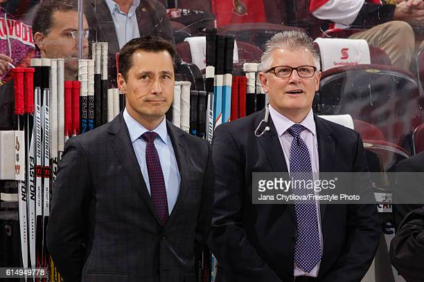 Head coach Guy Boucher and associate coach Marc Crawford of the Ottawa Senators look from the bench during player introductions prior to their home...