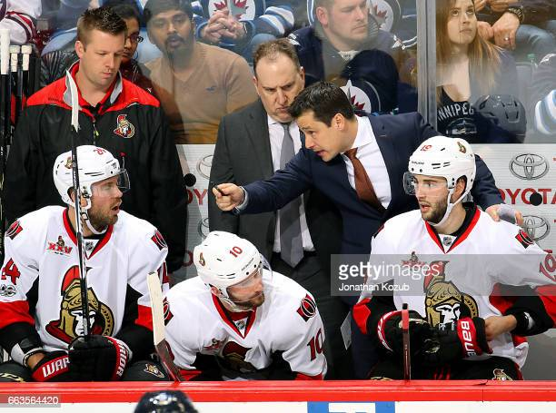 Head Coach Guy Boucher of the Ottawa Senators instructs Viktor Stalberg on the bench during second period action against the Winnipeg Jets at the MTS...