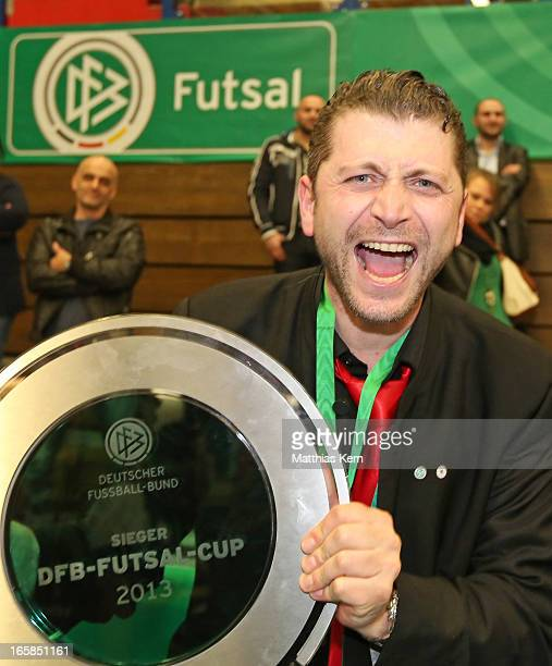 Head coach Hakan Karadiken of Hamburg poses with the cup after winning the DFB Futsal Cup final match between Hamburg Panthers and UFC Muenster at...