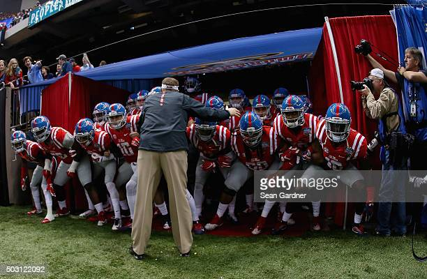 Head coach Hugh Freeze of the Mississippi Rebels and team enter the field before playing against the Oklahoma State Cowboys during the first quarter...