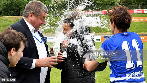 Head coach Inka Grings of Duisburg gets a shower from Linda Bresonik after winning the 2 Frauen Bundesliga Nord championship at PCCStadion on May 15...