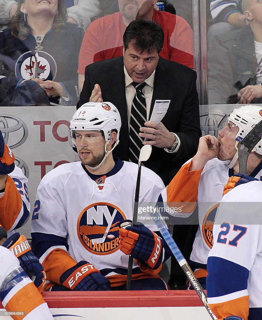 Head coach Jack Capuano of the New York Islanders gestures from the bench as he speaks in front of Josh Bailey in third period action in an NHL game...