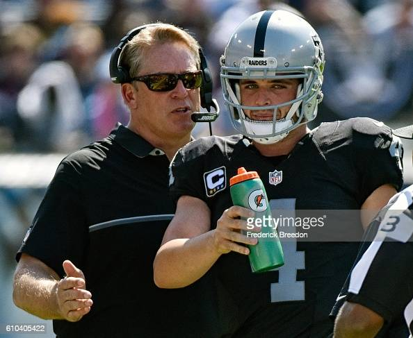 Head coach Jack Del Rio of the Oakland Raiders coaches quarterback Derek Carr during the first half of a game against the Tennessee Titans at Nissan...