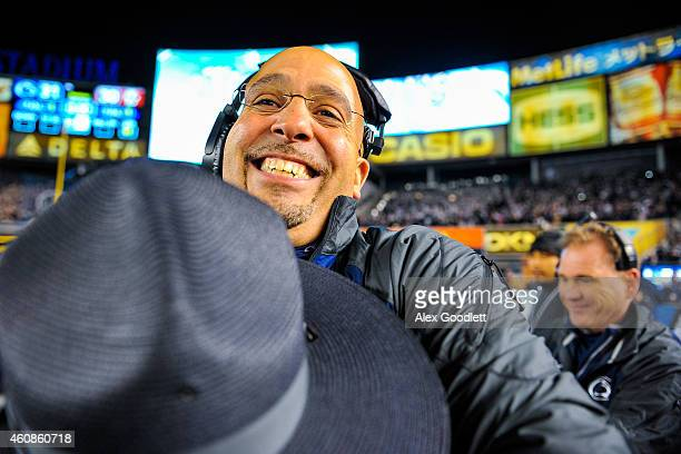 Head coach James Franklin of the Penn State Nittany Lions hugs a police officer after defeating the Boston College Eagles in the 2014 New Era...