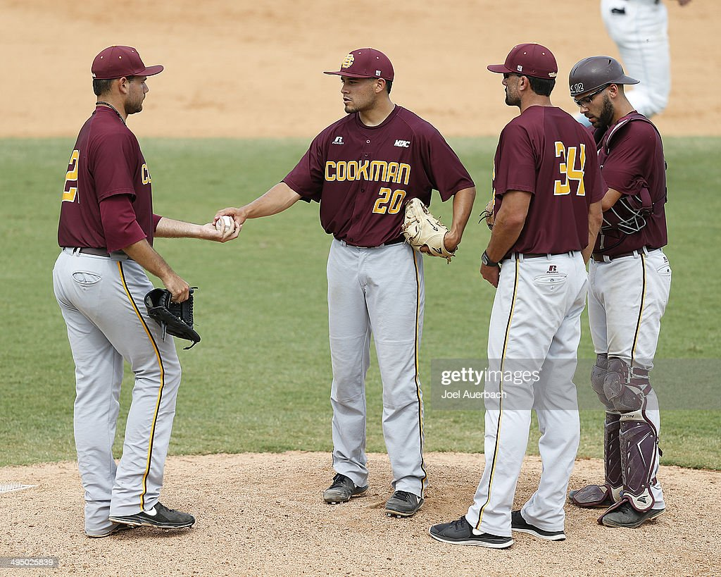 Head coach Jason Beverlin looks on as Keith Zuniga hands the ball to Christopher Waltermire of the BethuneCookman Wildcats during a pitching change...