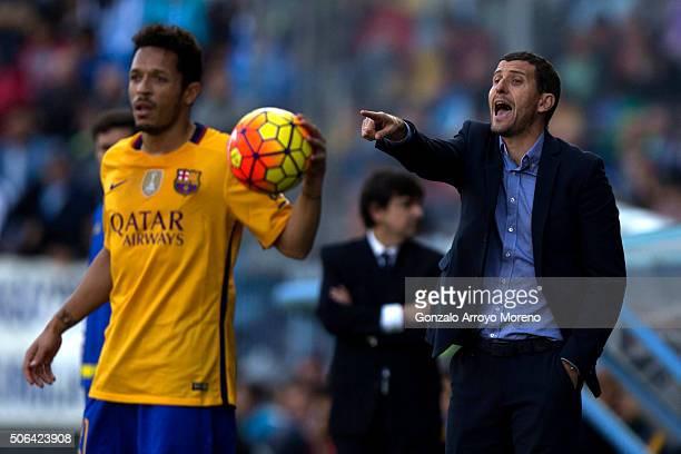 Head coach Javier Garcia Carlos of Malaga CF protests behind Adriano Correia Claro of FC Barcelonaduring the La Liga match between Malaga CF and FC...