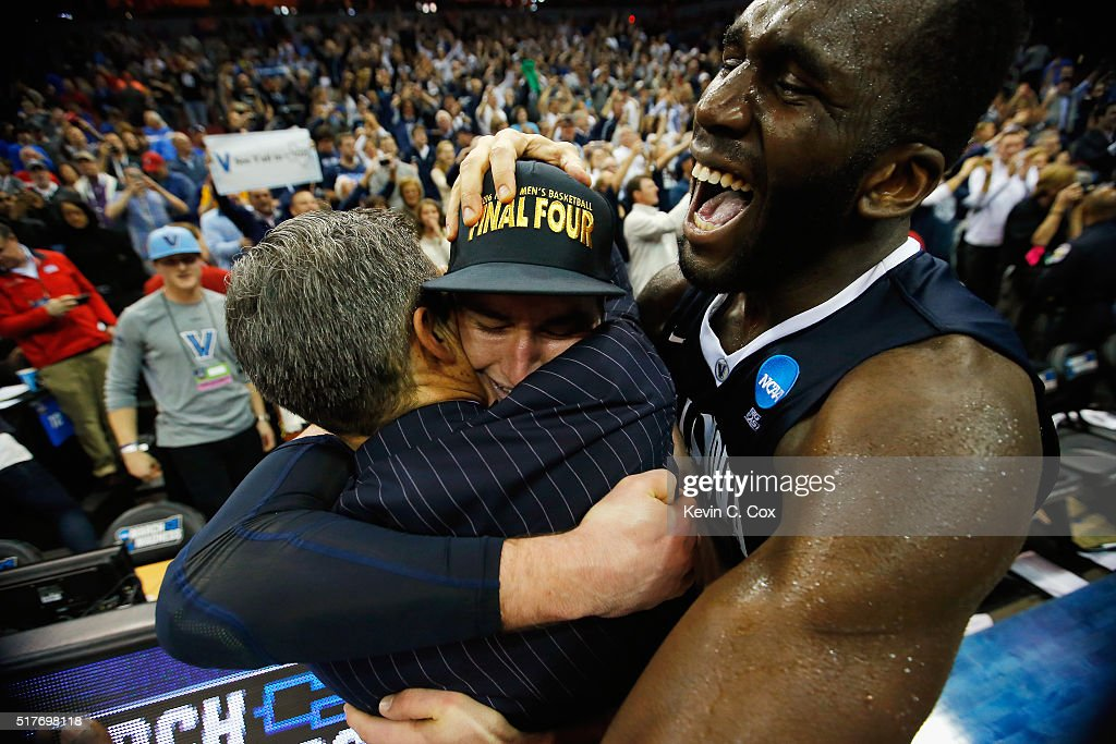 Head coach <a gi-track='captionPersonalityLinkClicked' href=/galleries/search?phrase=Jay+Wright&family=editorial&specificpeople=226981 ng-click='$event.stopPropagation()'>Jay Wright</a> of the Villanova Wildcats, <a gi-track='captionPersonalityLinkClicked' href=/galleries/search?phrase=Ryan+Arcidiacono&family=editorial&specificpeople=7887112 ng-click='$event.stopPropagation()'>Ryan Arcidiacono</a> #15, and <a gi-track='captionPersonalityLinkClicked' href=/galleries/search?phrase=Daniel+Ochefu&family=editorial&specificpeople=9986325 ng-click='$event.stopPropagation()'>Daniel Ochefu</a> #23 celebrate defeating the Kansas Jayhawks 64-59 during the 2016 NCAA Men's Basketball Tournament South Regional at KFC YUM! Center on March 26, 2016 in Louisville, Kentucky.