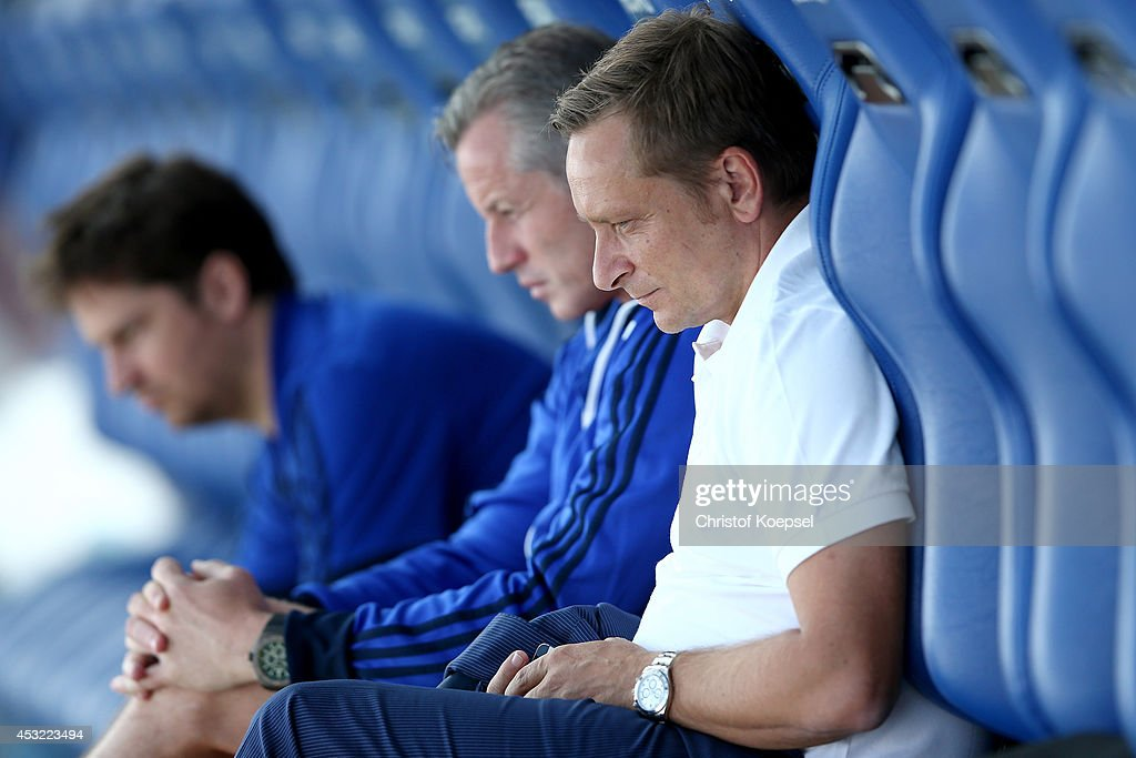 Head coach Jens Keller and manager Horst Heldt of Schalke sit on the bench prior to the pre-season friendly match between VfL Bochum and FC Schalke 04 at Rewirpower Stadium on August 5, 2014 in Bochum, Germany.