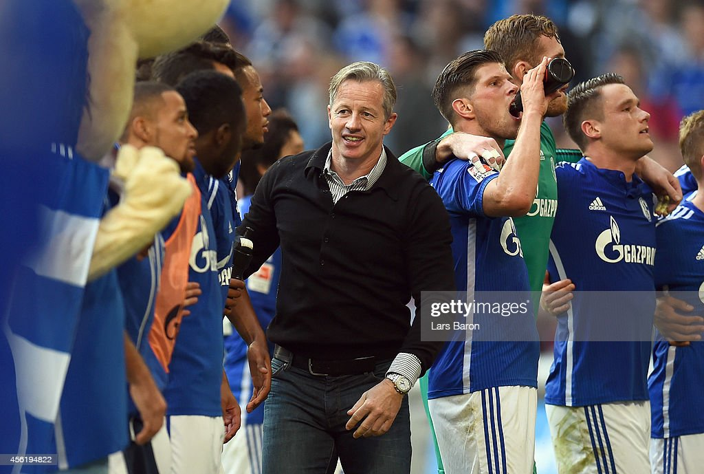 Head coach Jens Keller of Schalke celebrates with his players after winning the Bundesliga match between FC Schalke 04 and Borussia Dortmund at Veltins Arena on September 27, 2014 in Gelsenkirchen, Germany.