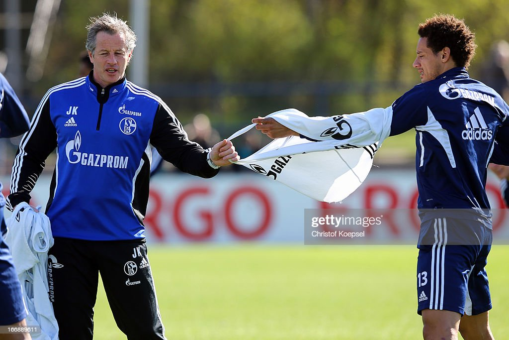 Head coach Jens Keller picks the training jersey of Jermaine Jones (R) during the FC Schalke 04 training session at their training ground on April 18, 2013 in Gelsenkirchen, Germany.