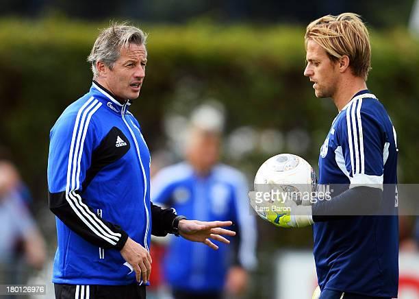 Head coach Jens Keller speaks with goalkeeper Timo Hildebrand during a FC Schalke 04 training session on September 9 2013 in Gelsenkirchen Germany
