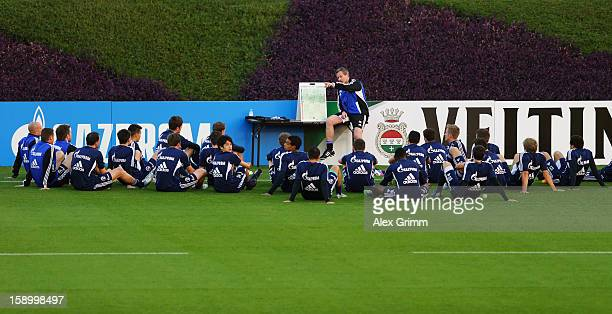 Head coach Jens Keller talks to the players during a Schalke 04 training session at the ASPIRE Academy for Sports Excellence on January 5 2013 in...